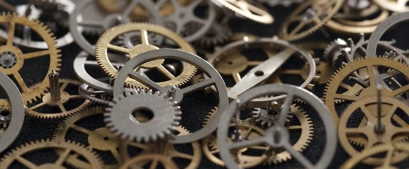 Selective Focus Close Up on Pile of Clock Parts, Assortment of Cogs and Gears in Variety of Sizes, Shapes and Metals